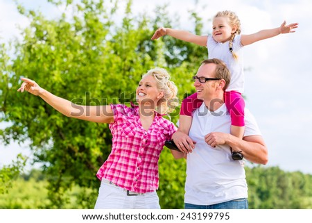 Family having summer walk on meadow outdoors - stock photo