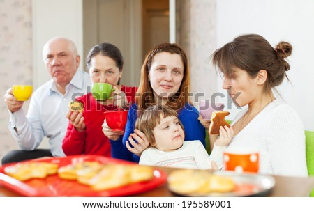 family having tea with cakes at home - stock photo