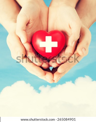 family health, charity and medicine concept - male and female hands holding red heart with cross sign - stock photo