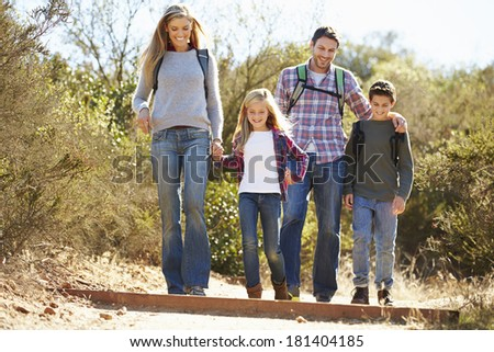 Family Hiking In Countryside Wearing Backpacks - stock photo