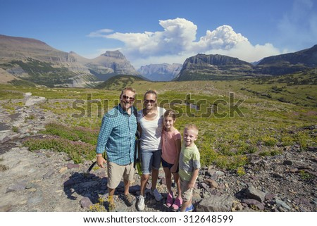 Family hiking in in the beautiful mountains of Glacier National Park  - stock photo