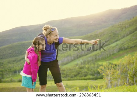 Family hiking in the mountains together. Young mother pointing out wildlife while she and her daughter take a hike together in the mountains on a beautiful summer evening - stock photo