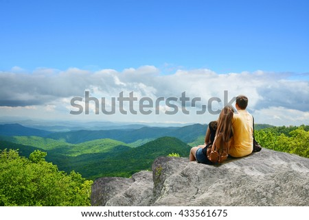 Family hiking trip. Father with arms around his daughter looking at beautiful summer mountains landscape. People siting on the top of mountain on rock. Blue sky in background. North Carolina, USA. - stock photo