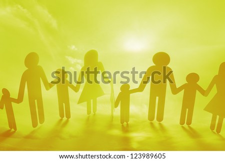 Family holding hands on yellow background - stock photo