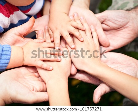 Family holding hands together closeup - stock photo