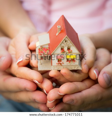 Family holding little house in hands. Real estate concept - stock photo