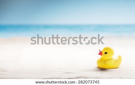 Family holiday concept with rubber ducks walking on the beach - stock photo