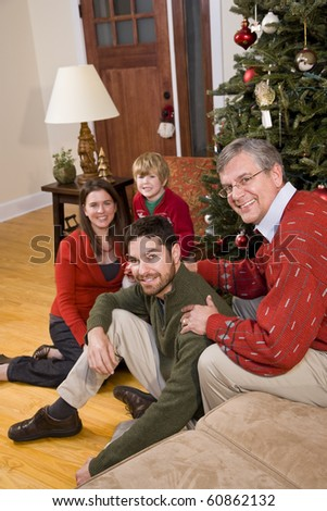 Family holiday portrait - grandfather with family sitting by Christmas tree - stock photo