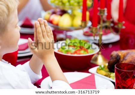 family, holiday, religion, thanksgiving, tradition and people concept - close up of boy praying at christmas dinner at home - stock photo