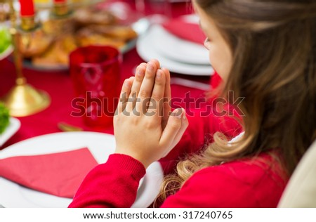 family, holiday, religion, thanksgiving, tradition and people concept - close up of girl praying at christmas dinner at home - stock photo
