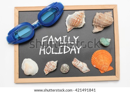 Family Holiday text on chalk board with swimming goggle and shell - vacation and business concept - stock photo