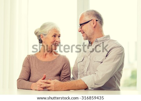 family, holidays, age and people concept - happy senior couple sitting on sofa at home