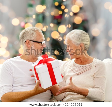 family, holidays, age and people concept - happy senior couple with gift box over christmas tree lights background - stock photo