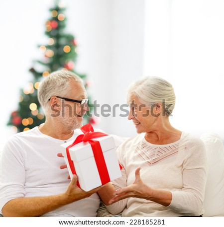 family, holidays, age and people concept - happy senior couple with gift box over living room and christmas tree background