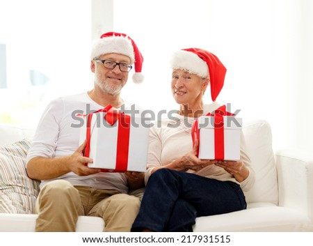 family, holidays, christmas, age and people concept - happy senior couple in santa helper hats with gift boxes at home