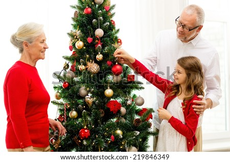 family, holidays, generation and people concept - smiling family decorating christmas tree at home - stock photo