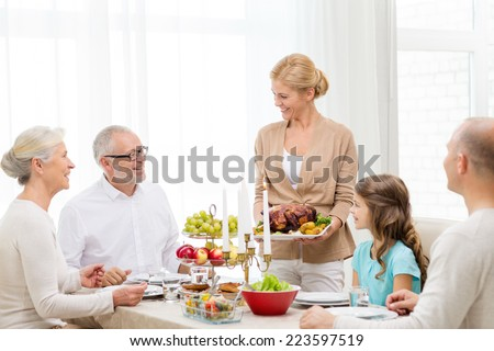 family, holidays, generation and people concept - smiling family having dinner at home - stock photo