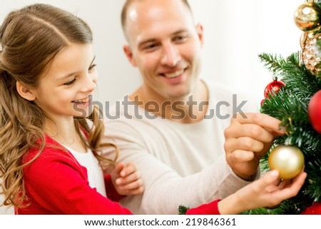family, holidays, generation and people concept - smiling girl with father decorating christmas tree at home - stock photo