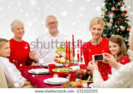 family, holidays, generation, christmas and people concept - smiling family having dinner and taking photo with camera at home - stock photo
