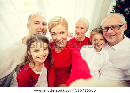 family, holidays, generation, christmas and people concept - smiling family with camera or smartphone making selfie at home