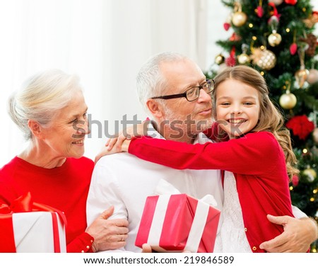 family, holidays, generation, christmas and people concept - smiling grandparents and granddaughter with gift boxes sitting on couch at home - stock photo