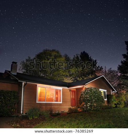 Family home at night underneath the stars - stock photo