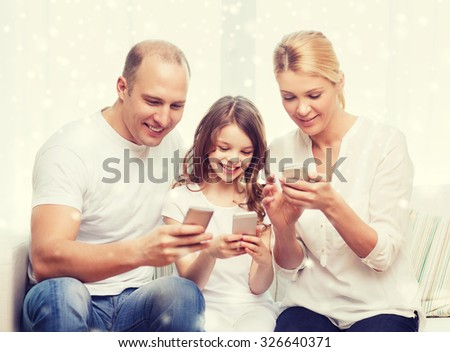 family, home, technology and people concept - smiling mother, father and little girl with smartphones over snowflakes background
