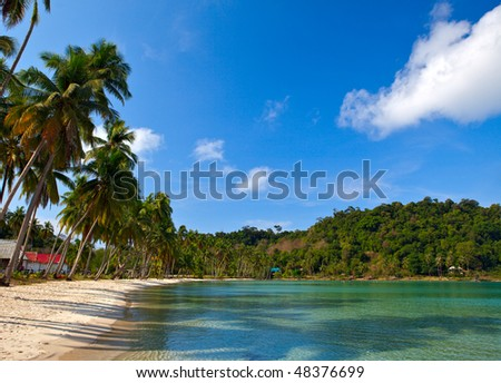 Family hotel on the tropical beach with white sand near sea water and blue sky
