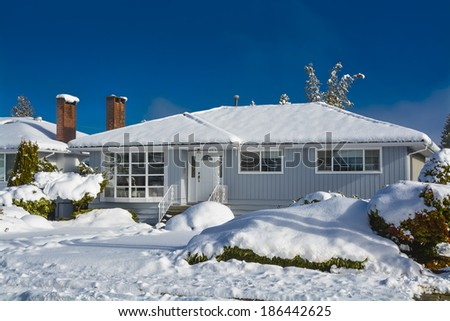Family house at winter season. Residential house in snow on a sunny day. Grey house in snow on blue sky background. - stock photo
