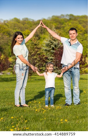 Family house concept: parents holding hands under their daughter