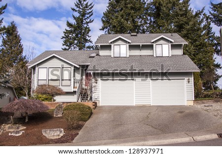 family house with landscaping on the front and blue sky on background
