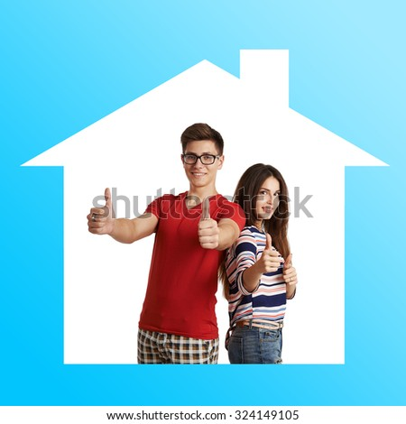 Family housing concept. Happy smiling couple showing thumbs up in new house.