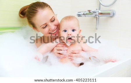 family in a bath with foam mother together baby son - stock photo