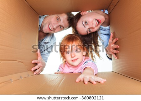 Family in a cardboard box ready for moving house - stock photo