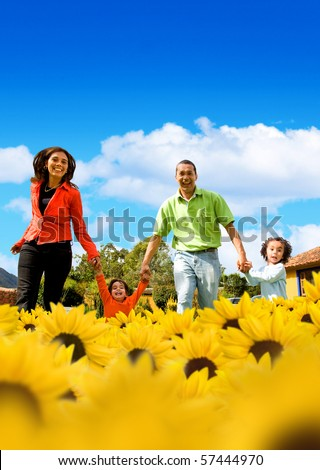 Family in a field of beautiful yellow sunflowers with a blue sky on the background - stock photo