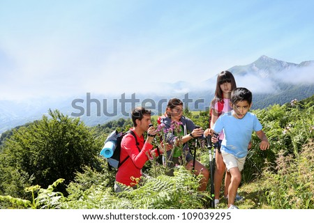 Family in a hikking day climbing up the hill - stock photo