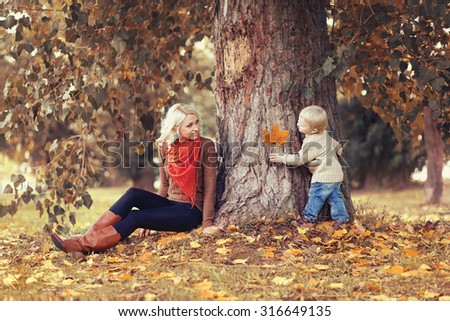 Family in autumn park! Mom playing with son child  - stock photo