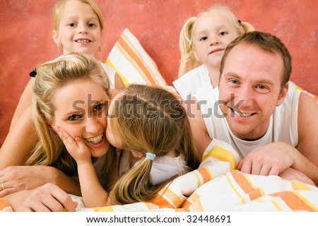Family in bed in the morning, daughter kissing and hugging her mother - stock photo