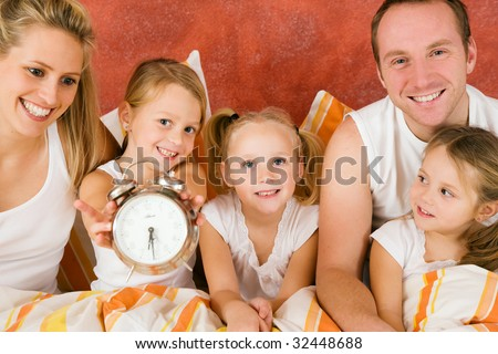 Family in bed in the morning, on child holding a clock â?? metaphor for getting up to enjoy the day - stock photo