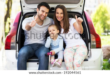 Family in car showing thumbs up - stock photo