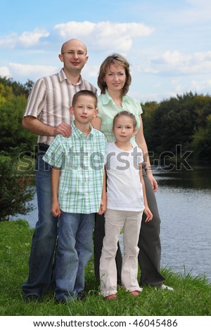 family in early fall park. father, mother, little boy and girl is staying near pond. - stock photo
