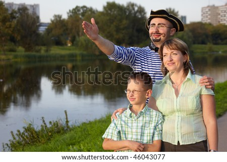 family in fall evening park near pond: man in pirate suit, woman and little boy. man is point away - stock photo