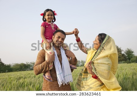 Family in field with girl on father's shoulders - stock photo