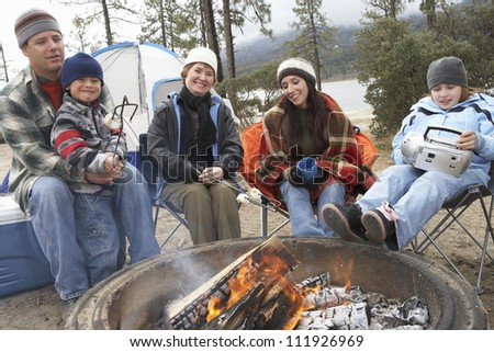Family in front of campfire ready to toast marshmallow - stock photo