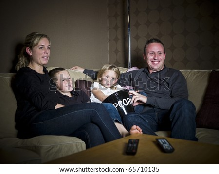 Family in front of the Television sitting in a sofa - stock photo