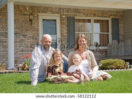 Family in Front of Their Home - stock photo