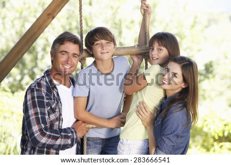 Family In Garden By Treehouse - stock photo