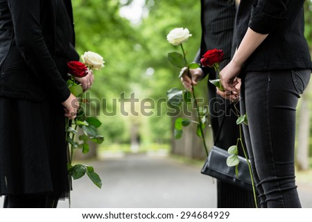 Family in guard of honor at funeral, only torso of people to be seen - stock photo