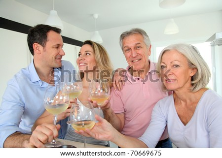 Family in home kitchen drinking wine - stock photo