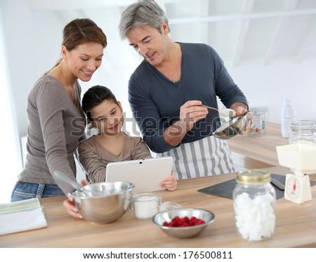 Family in home kitchen preparing pastry - stock photo